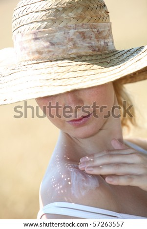 Closeup of beautiful woman spreading sunscreen on her shoulder - stock photo