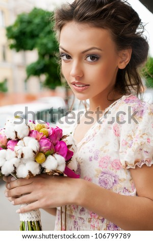 Closeup of beautiful woman with bouquet of flowers. Outdoors - stock photo