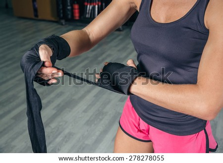 Closeup of beautiful woman wrapping his hands with protective bandages before boxing training in the gym - stock photo