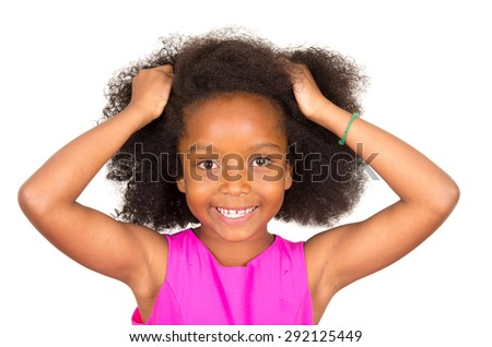 Closeup of beautiful young black girl with afro and pink dress holding hands on head looking to camera smiling - stock photo