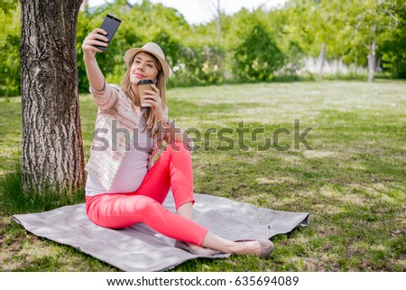 Closeup of beautiful young blonde Caucasian woman in black coat taking a selfie with smart phone in park. Selfie time. Beautiful young girl taking a selfie at the park.