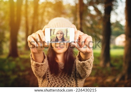 Closeup of beautiful young Caucasian brunette woman taking a selfie with smartphone in park in autumn wearing beige knitted hat and sweater. - stock photo