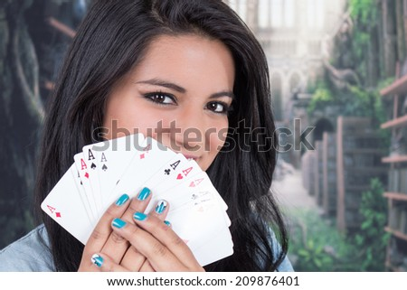 Closeup of beautiful young girl holding ace cards from a deck of cards - stock photo