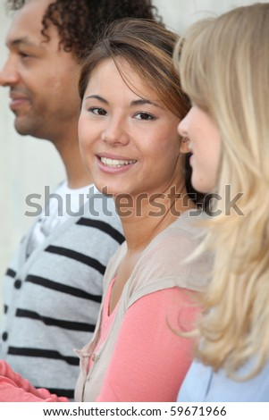Closeup of beautiful young woman amongst group friends