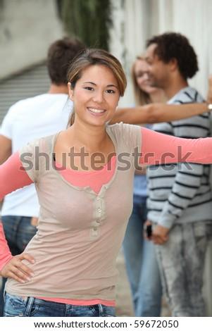 Closeup of beautiful young woman amongst group friends - stock photo