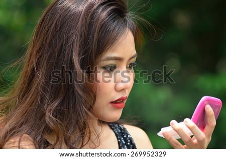 closeup of beautiful young woman applying red lipstick - stock photo