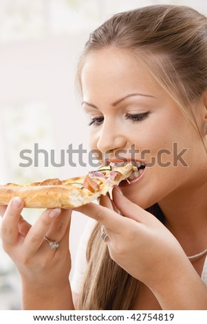 Closeup of beautiful young woman eating pizza slice.
