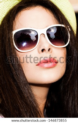 closeup of beautiful young woman in bright summer hat and sunglasses - stock photo