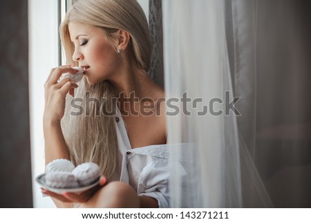 Closeup of beautiful young woman sitting near window at home and holding in hands plate of mashmellows, happy lifestyle - stock photo