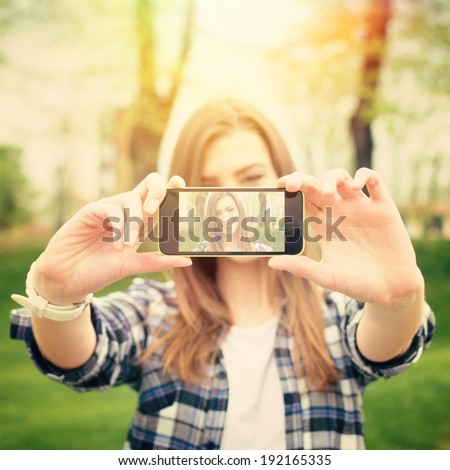 Closeup of beautiful young woman taking a selfie photo with smart phone outdoors on sunny summer day. Instant filter. Square image. - stock photo