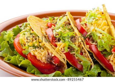 Closeup of beef tacos served with salad and fresh tomatoes salsa on white background - stock photo