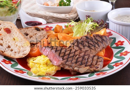 Closeup of beefsteak  with french fries and vegetables - stock photo