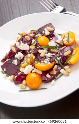 Closeup of beet, cumquats, feta cheese and pine nuts salad with chives