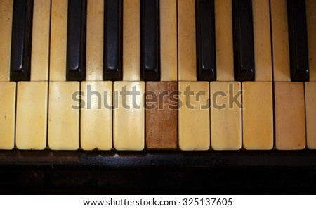 Closeup of black and white piano keys and wood grain with vintage sepia tone one ragged keys. - stock photo