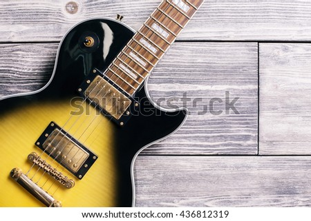Closeup of black and yellow electric guitar on wooden background - stock photo