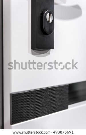 Closeup of black keyhole in white door