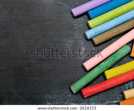 closeup of blackboard with pieces of coloured crayons - stock photo