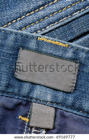 Closeup of blank dark cotton labels inside of blue worn jeans, kind of textured background - stock photo