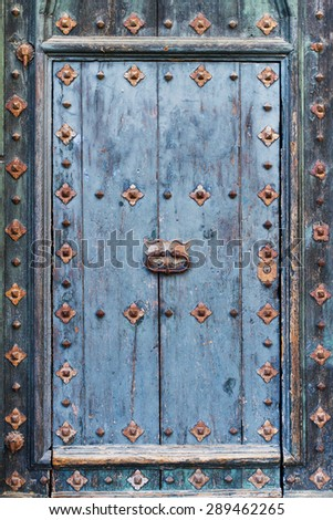 Closeup  of blue ancient wooden door with rusty decorations - stock photo