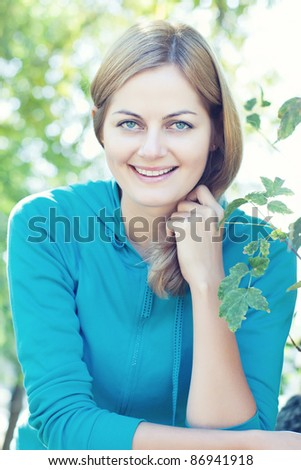 Closeup of blue-eyed smiling woman against blurred background outdoors with selective focus - stock photo