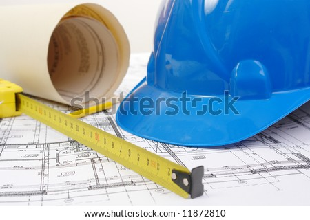 Closeup of blue hard hat, yellow pencil, measuring tape and building plans - stock photo