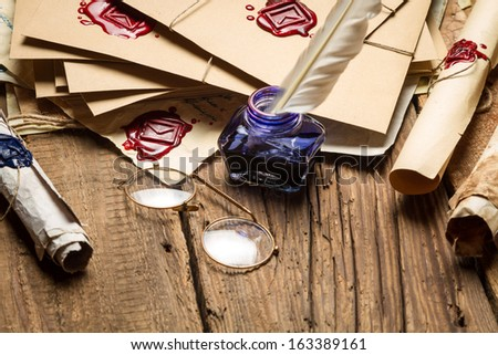 Closeup of blue inkwell and glasses on table filled with old messages - stock photo