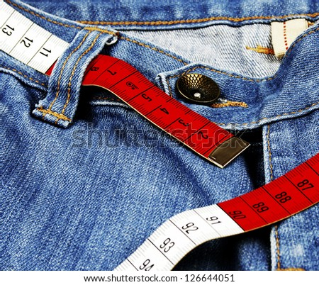 Closeup of blue jeans and measure tape isolated - stock photo