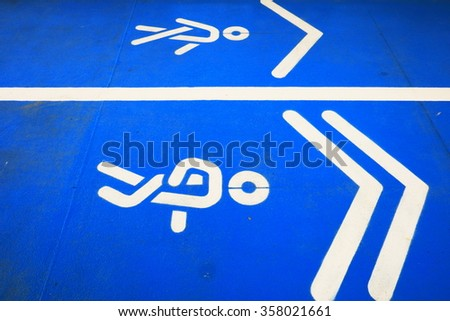 Closeup of blue running race track with two white rubber signs for slow running and walking.