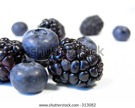 closeup of blueberries and blackberries isolated on white in scattered