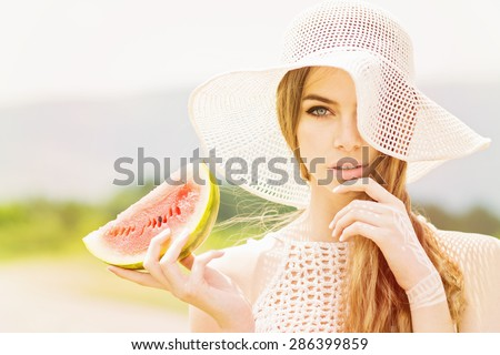 Closeup of bohemian fashion beautiful young Caucasian blonde woman with beige crochet hat and top holding a watermelon slice. Attractive girl with blue eyes and hand body paint outdoors portrait.  - stock photo
