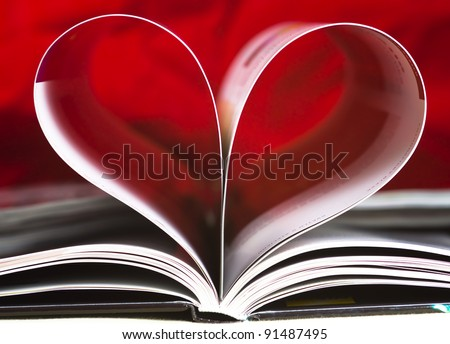 Closeup of book pages folded into a heart shape - stock photo