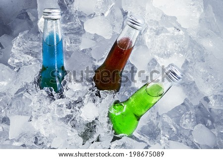 Closeup of bottles of beer sink on ice cube - stock photo