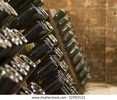 Closeup of bottles of wine aging in an old cellar