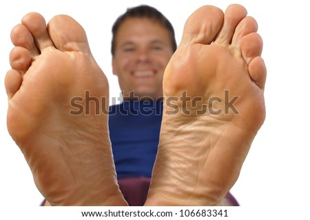 Closeup of bottom of feet as smiling man reclines on white background