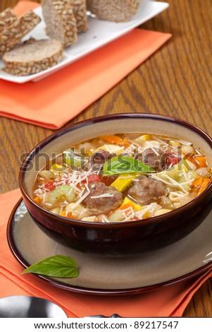 Closeup of bowl of hot fresh Italian Meatball Soup and wholegrain bread - stock photo