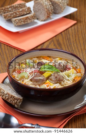 Closeup of bowl of hot fresh Italian Meatball Soup and wholegrain bread - stock photo