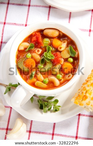 Closeup of bowl of hot fresh Minestrone soup and cheese garlic breadsticks - stock photo