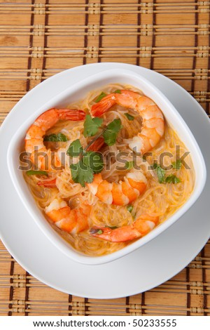 Closeup of bowl of Prawn Laksa soup with rice noodles, shrimps garnished with fresh cilantro.