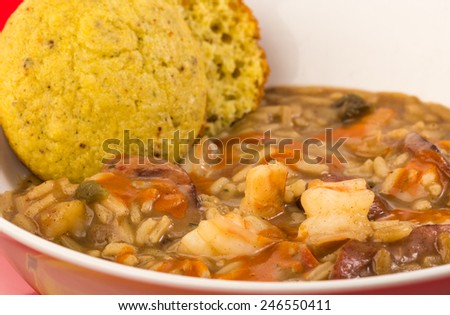 Closeup of bowl of spicy cajun shrimp and sausage gumbo with cornbread muffin. - stock photo