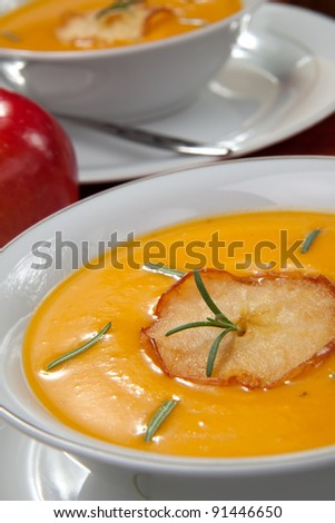 Closeup of bowls of hot delicious pumpkin soup with roasted apples, and rosemary. - stock photo