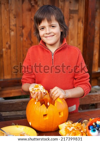 Closeup of boy carving a pumpkin Halloween jack-o-lantern - removing the seeds - stock photo