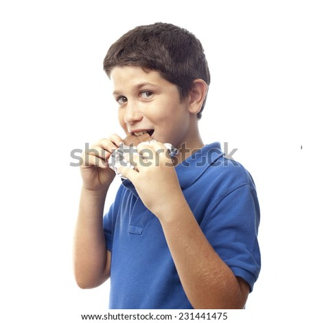 closeup of boy eating chocolate bar - stock photo