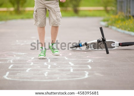 Closeup of boy's legs and hopscotch drawn on asphalt. Child playing hopscotch on playground outdoors on a sunny day. outdoor activities for children. - stock photo
