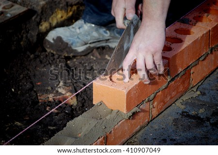 Closeup of bricklayer during the building of a house extension. - stock photo