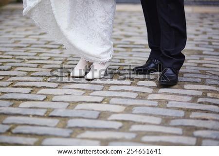 Closeup of bride and groom feet - stock photo