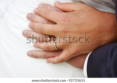 Closeup of bride and groom hands showing wedding rings - stock photo