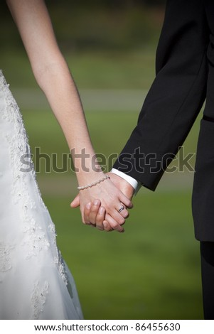 Closeup of Bride and groom holding hands - stock photo