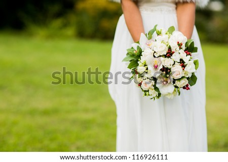 closeup of bride hands holding beautiful wedding bouquet - stock photo