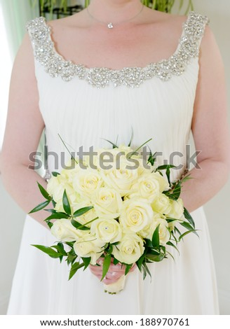 Closeup of bride holding flower arrangement with yellow roses
