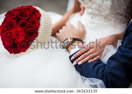 Closeup of bride in a elegant white dress and with a rose bouquet holding groom's stylish hand with luxury watch - stock photo